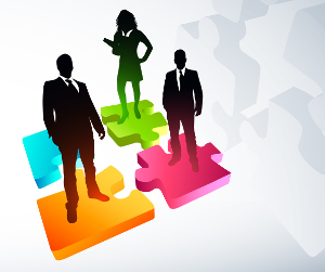 Silhouettes of business leaders standing on colorful puzzle pieces