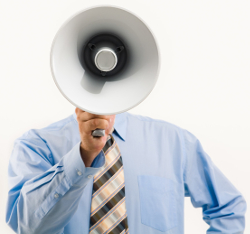 Photo of a man in a blue shirt and striped tie, face obscured by a bullhorn