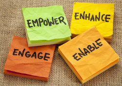 Photo of sticky notes with the words enable, engage, empower, enhance