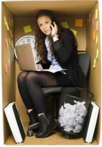 Photo of a businesswoman, including her laptop & office equipment, squashed into a small cardboard box