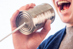 Closeup photo of someone holdinmg a can with a cord and shouting into it.