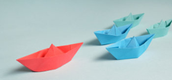 Photo of red paper boat leading the way for blue and green boats