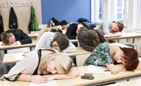 Photo of a class of adult students asleep with their heads on the desks