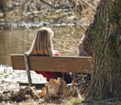 Photo of woman sitting on a bench by a tree looking out over a river
