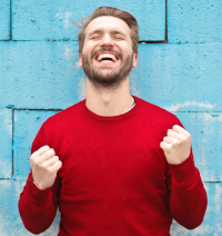 Photo of a very happy man in a red sweater standing before a blue block wall