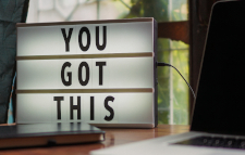 "Electric sign reading ""You got this"" in black letters on a desk with a phone and computer"