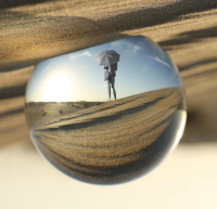 Photo of a person standing on a sand dune within a crystal ball