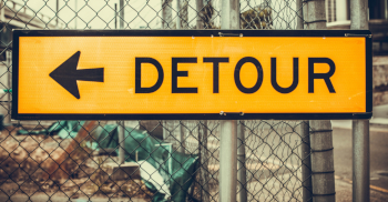 Photo of a yellow-and-black DETOUR sign on a chain-link fence