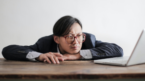 Photo of bored-looking man wearing glasses and a suit with chin on hands staring at a laptop screen