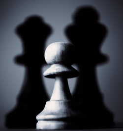 Grayscale photo of a wooden chess pawn with two shadows