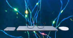 Photo of a phone, closed laptop (with a pair of glasses on top) and a mouse floating in space before a blue background with fairy lights