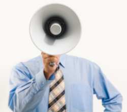 Photo of a businessman in shirt and tie holding a bullhorn in front of his face