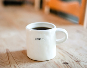 Photo ofcoffee mug with the word BEGIN on a wooden table