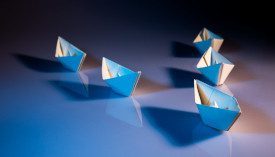 Photo of four origami boats following the lead of a fifth
