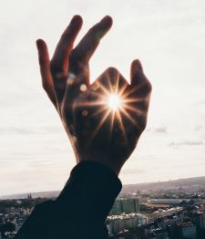 Photo of a hand encircling the sun