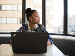 Photo of a Black businesswoman sitting in front of a laptop, gazing thoughtfully out the office window