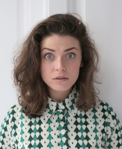 Photo of a white woman with shoulder-length brown hair wearing a print blouse and with her eyes wide open and startled