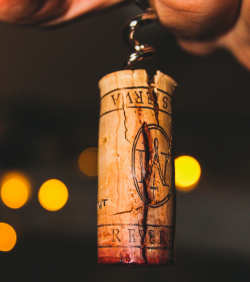 Photo of a wine cork with the corkscrew in it, against a dark background with blurry orange lights