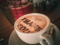 "Photo of a cup of coffee with ""THANK YOU"" written in the foam"