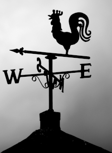 Grayscale photo of a rooster weathervane