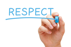 Photo fo a hand writing RESPECT in blue marker
